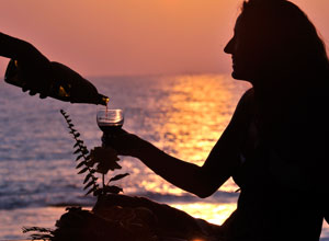 Enjoy a drink as the sun sets over the Bay of Bengal